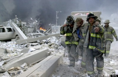 UNITED STATES - SEPTEMBER 11: Firefighters Todd Heaney and Frankie DiLeo, of Engine 209, carry injured firefighter from the rubble of the World Trade Center., (Photo by Todd Maisel/NY Daily News Archive via Getty Images)